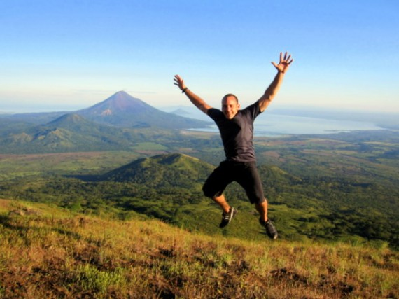 Jumping for joy on top of volcano El Hoyo